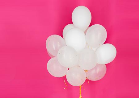 concepto de fiesta, cumpleaños, fiesta y decoración - cerca de inflado de globos de helio blancos sobre fondo rosa