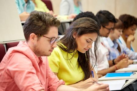éducation, lycée, université, l'apprentissage et les gens concept - groupe d'étudiants internationaux avec les ordinateurs portables au cours d'écriture