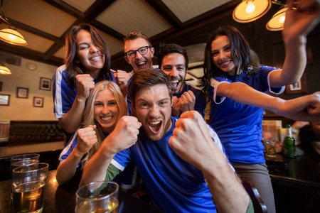 sport, people, leisure, friendship and entertainment concept - happy football fans or friends drinking beer and celebrating victory at bar or pub Banco de Imagens