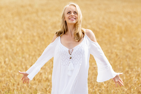 woman looking: country, nature, summer holidays, vacation and people concept - smiling young woman in white dress on cereal field