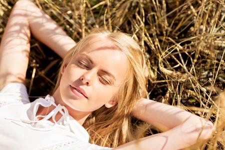 haymow: nature, summer holidays, vacation and people concept - happy young woman lying and enjoying sun on cereal field or hay