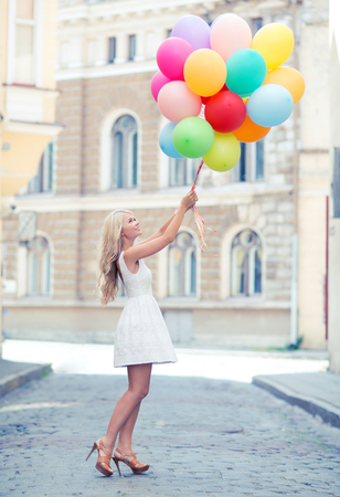 flying woman: summer holidays, celebration and lifestyle concept - beautiful woman with colorful balloons in the city