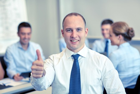 success man: business, people, gesture and teamwork concept - smiling businessman showing thumbs up with group of businesspeople meeting in office