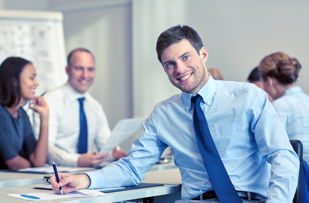 teamwork people: business, people and teamwork concept - smiling businessman with group of businesspeople meeting in office Stock Photo