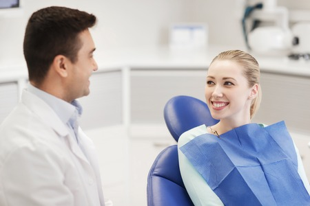 health care and medicine: people, medicine, stomatology and health care concept - happy male dentist with woman patient talking at dental clinic office