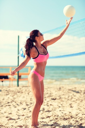 summer sport: summer vacation, sport and people concept - young woman with ball playing volleyball on beach Stock Photo