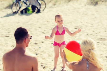 small girl: family, summer vacation, adoption and people concept - close up of happy man, woman and little girl playing with inflatable ball on beach