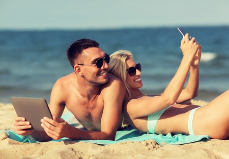 family vacation: love, travel, tourism, technology and people concept - happy couple on vacation with tablet pc computer and smartphone sunbathing on summer beach