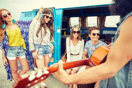 summer holidays, road trip, vacation, travel and people concept - happy young hippie friends having fun and playing music over minivan car Stock Photo