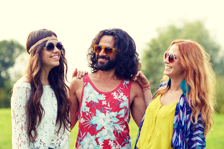 nature, summer, youth culture and people concept - smiling young hippie friends in sunglasses talking outdoors Stock Photo