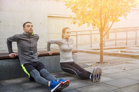 triceps: fitness, sport, exercising, training and people concept - couple doing triceps dip exercise on city street bench