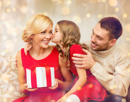 adorable child: family, christmas, x-mas, winter, happiness and people concept - adorable child kisses her mother and gives present Stock Photo