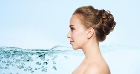 cabeza femenina: la salud, las personas, la cirugía plástica y el concepto de belleza - la cara de mujer joven y hermosa sobre fondo azul con salpicaduras de agua Foto de archivo
