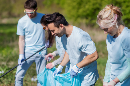 public welfare: volunteering, charity, cleaning, people and ecology concept - group of happy volunteers with garbage bags cleaning area in park