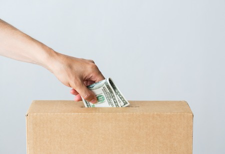 charity, finances, funding, investment and people concept - male hand putting dollar money into donation box Stock Photo