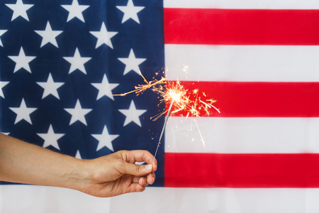 american independence day, patriotism, holidays and people concept - close up of hand holding sparkler over national flag Stock Photo
