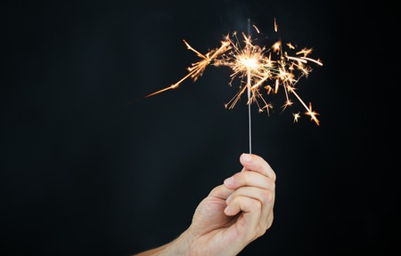 pyrotechnics: christmas, holidays, new year party and pyrotechnics concept - male hand holding sparkler or bengal light burning over black background Stock Photo