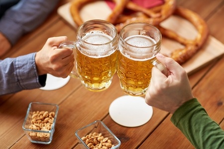 people, leisure and drinks concept - close up of male hands clinking beer mugs and pretzels at bar or pub