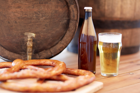 alehouse: brewery, drinks and alcohol concept - close up of old beer barrel, glass, bottle and pretzel on wooden table