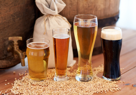 alehouse: brewery, drinks and alcohol concept - close up of old beer barrel, glasses and bag with malt on wooden table Stock Photo