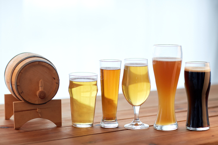 brewery, drinks and alcohol concept - close up of different beers in glasses and barrel on table Stock Photo