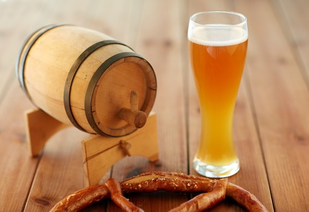 alehouse: brewery, drinks and alcohol concept - close up of draft lager beer in glass, pretzel and wooden barrel on table Stock Photo