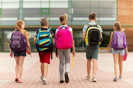 主な教育、友情、幼年期および人々 コンセプト - 野外を歩いている後ろからバックパックで幸せな小学生のグループ