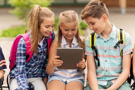educación primaria, la amistad, la infancia, la tecnología y el concepto de personas - grupo de estudiantes de la escuela primaria felices con mochilas sienta en banco y hablando al aire libre Foto de archivo