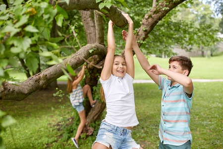 climb: friendship, childhood, leisure and people concept - group of happy kids or friends hanging on tree and having fun in summer park