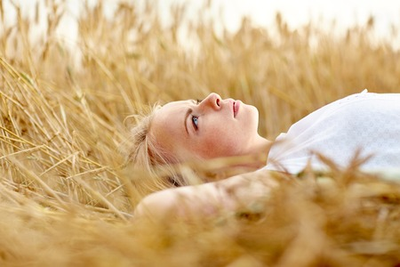 nature, summer holidays, vacation and people concept - young woman or teenage girl lying and dreaming on cereal field Stock Photo