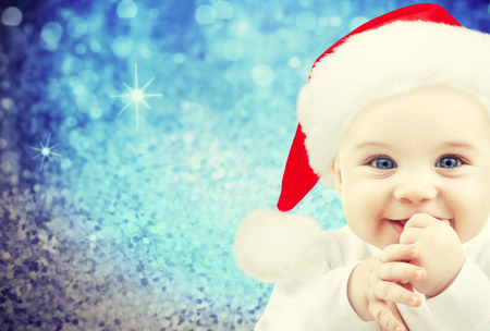 christmas, babyhood, childhood and people concept - happy baby in santa hat over blue glitter holidays lights background photo