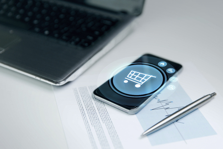 shopper: business, technology, sale and commerce concept - close up of smartphone with shopping cart on screen, laptop computer and chart with pen on office table