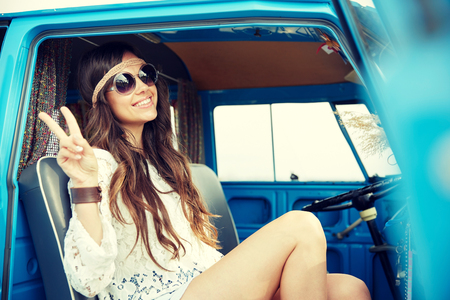 summer holidays, road trip, vacation, travel and people concept - smiling young hippie woman showing peace gesture in minivan car Stock Photo