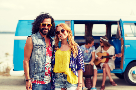 trip over: summer holidays, road trip, vacation, travel and people concept - smiling young hippie couple with friends over minivan car