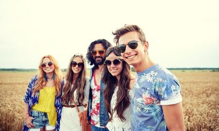 pareja de adolescentes: naturaleza, verano, la cultura juvenil y la gente concepto - smiling amigos hippies en campo de cereales