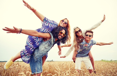 hippy: nature, summer, youth culture and people concept - happy young hippie friends having fun on cereal field