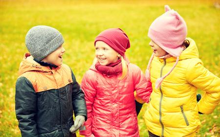 niños platicando: childhood, leisure, friendship and people concept - group of happy children in autumn park Foto de archivo