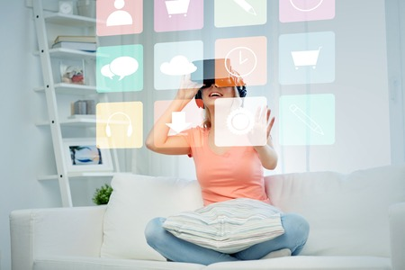 mediated: technology, augmented reality, multimedia and people concept - happy young woman in virtual headset or 3d glasses and headphones playing game at home looking at menu icons