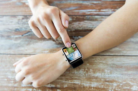 web screen: business, modern technology, media, internet and people concept - close up of female hands setting smart watch with news web page on screen on wooden table