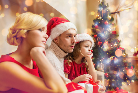economic depression: family, christmas, x-mas, winter and people concept - unhappy family at home with many gift boxes
