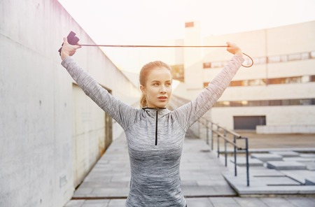 woman rope: fitness, sport, people, exercising and lifestyle concept - woman skipping with jump rope outdoors