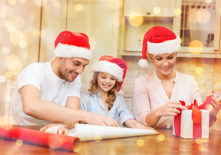 christmas, x-mas, winter,family, happiness and people concept - smiling family in santa helper hats with gift box