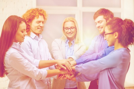 black hands: business, office, gesture and startup concept - smiling creative team with hands on top of each other sitting in office Stock Photo