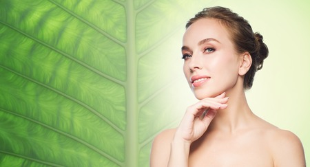 natural beauty: beauty, people and health concept - beautiful young woman touching her face over natural green leaf background