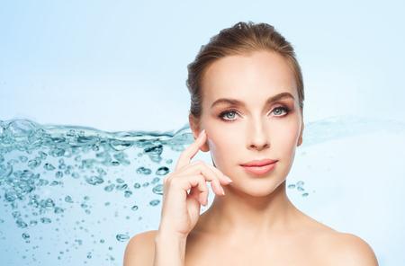 la beauté, les gens et le concept de chirurgie plastique - belle jeune femme montrant sa pommette sur fond bleu avec des éclaboussures d'eau