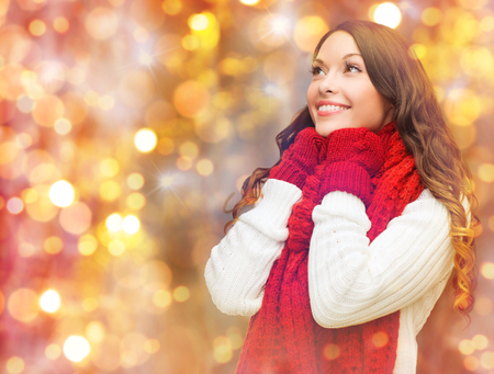 christmas lights background: winter, people, christmas and holidays concept - happy smiling woman in scarf and mittens over lights background