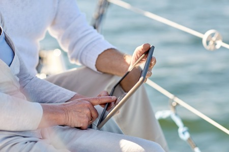 sailing, technology, tourism, travel and people concept - close up of senior couple with tablet pc computer on sail boat or yacht deck floating in sea