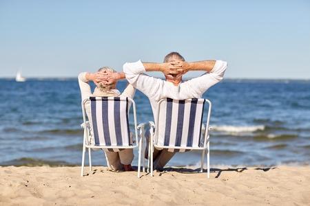 夏のビーチでデッキチェアに座って幸せな先輩カップル家族、年齢、旅行、観光、人コンセプト 写真素材