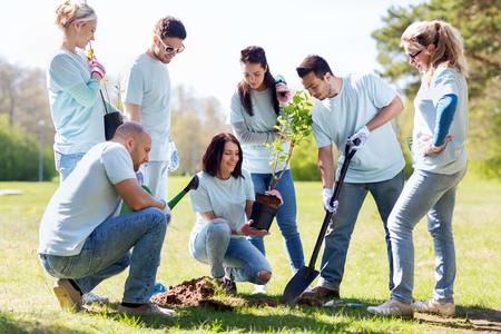 il volontariato, la carità, la gente e concetto di ecologia - gruppo di volontari felici piantagione di alberi e il foro di scavo con pala nel parco