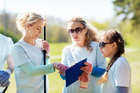 志愿者,慈善,人物和生态概念 - 志愿者志愿者与剪贴板在公园里
